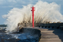Breakwater Storm. Powerful wave breaking against a breakwater during a storm in the Baltic sea in the port of Ustka Stock Photo