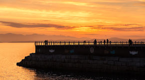 Breakwater sunset. A brilliant sunset illuminates the breakwater in Victoria BC , Canada. Walkers and joggers move along the breakwater that shelters the Royalty Free Stock Image