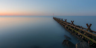 Breakwater at sunset. A breakwater, in a very calm sea, at sunset.  Long exposure Stock Photo