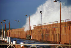 Breakwater swell. Massive wave collides with a breakwater pier Royalty Free Stock Photo