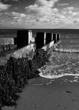 Breakwaters beach defences black and white. Photo taken at Swanage bay in Kent England of a wave breaking against the breakwater sea defences Royalty Free Stock Photos