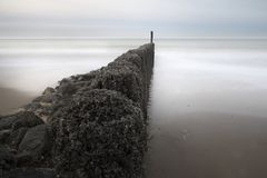 Breakwaters on the coast in Zeeuws-Vlaanderen, Zeeland, the Netherlands. Breakwaters on the beach.. They protect the underlying dike against the sometimes heavy Royalty Free Stock Image