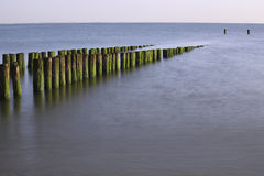 Breakwaters at the coast, Zeeland, The Netherlands. Breakwaters at the coast photographed on a warm summer evening. This photograph was made in Zeeland, The stock photo