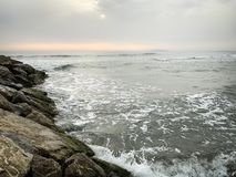 Breakwaters Made Of Rock Breaking Sea Waves. Coastal breakwaters made of natural rock blocks calming down incoming waves in the mediterranean sea. The sun is royalty free stock photos