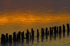 Breakwaters at an orange sunset Stock Photo