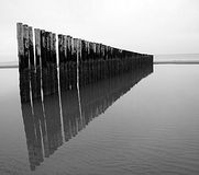 Breakwaters reflecting in the sea- Black and white photo Stock Photo