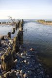 Breakwaters in sea. Scenic view of old wooden breakwaters receding in sea with calm water in foreground Royalty Free Stock Photography