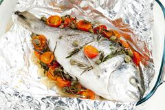 Bream baked with herbs and cherry tomatoes. Inside, indoor, indoors, interior, interiors, gastronomy, cuisine, foodstuff, meal, meals, nutrition, nourishment royalty free stock images