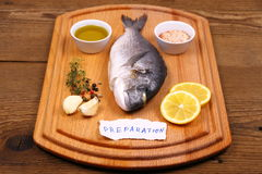 Bream fish on cutting board, preparation label Royalty Free Stock Image