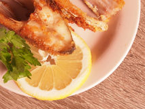 Bream. Fried in breadcrumbs on a plate with parsley and lemon Royalty Free Stock Photo