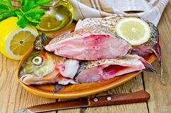 Bream raw in a clay plate with a lemon on the board Royalty Free Stock Photos