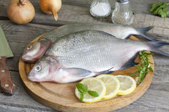 Bream raw fish on cutting board. In the kitchen with spices Royalty Free Stock Photos