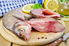 Bream raw on a round board with a knife and oil Stock Photography