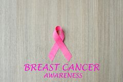 Breast Cancer Awareness. Pink Ribbon on wooden background for supporting people living and illness. Woman Healthcare and World cancer day concept stock photo