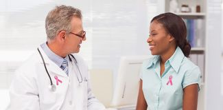 Composite image of breast cancer awareness message. Breast cancer awareness message against doctor speaking with cheerful young patient royalty free stock photo