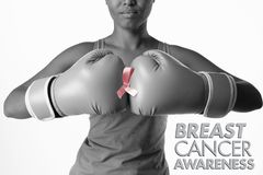 Composite image of breast cancer awareness message. Breast cancer awareness message against woman for breast cancer awareness with ribbon in boxing gloves stock images