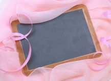 Breast Cancer Awareness month. Pink chiffon and ribbon swirl around a blank blackboard for your message. Good for breast cancer awareness month in October royalty free stock image