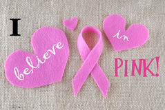 Breast Cancer Awareness month. Pink ribbon cut out of felt with heart decoration on burlap with message for breast cancer awareness month in October stock image