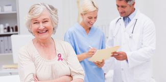 Composite image of breast cancer awareness ribbon. Breast cancer awareness ribbon against patient smiling while doctor and nurse discussing in clinic Stock Image