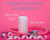 Breast Cancer Awareness Ribbon with Candle Flame Stethoscope. Burning light pink candle with stethoscope wrapped around it pink and white curling ribbon with Royalty Free Stock Photo
