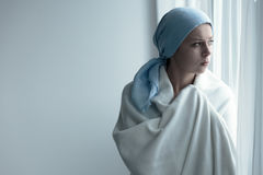 Breast cancer patient in blanket. Breast cancer survivor covering herself in white blanket, and looking out the window stock photo