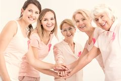Breast cancer unity and friendship. Happy women of different age groups joining hands and wearing pink ribbons stock photography