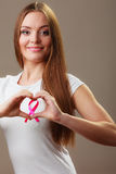 Breast cancer. Woman making heart shape on pink ribbon Stock Images