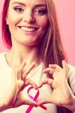 Breast cancer. Woman making heart shape on pink ribbon Royalty Free Stock Photography