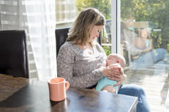 Breast feeding baby. A mother Breast feeding his baby at home Royalty Free Stock Photo