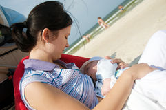 Breast feeding on the beach. Mother breast feeding her newborn on the beach. Horizontal shot royalty free stock photography