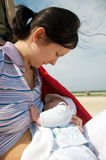 Breast feeding on the beach. Mother breast feeding her newborn on the beach. Vertical shot stock photography