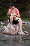 Breast feeding in river. Breast feeding baby on a rock in a river royalty free stock photo