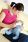 Breast feeding on sofa Royalty Free Stock Image