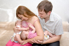 Breast feeding two little sisters twin Stock Images