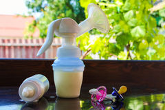 Breast pump, bottle of milk and pacifiers Stock Image