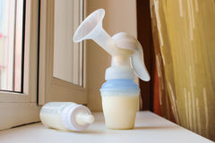 Breast pump and bottle of milk on the windowsill Stock Photos
