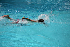Breast stroking. Boy swimming in a pool doing the breast stroke stock images