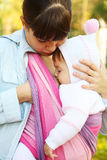Breastfeeding. Walk with the child in a baby sling. Breastfeeding stock image