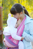 Breastfeeding. Walk with the child in a baby sling. Breastfeeding royalty free stock photography
