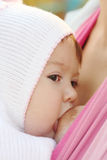 Breastfeeding. Walk with the child in a baby sling. Breastfeeding stock photography