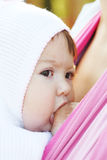 Breastfeeding. Walk with the child in a baby sling. Breastfeeding royalty free stock images