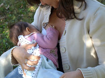 Breastfeeding. Pretty young brunette mum breastfeeding her baby Stock Photography