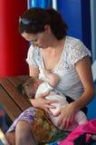 Breastfeeding in public. GOLD COAST - OCT 15 2014:Young women breastfeeding her baby (Naomi Ben-Ari age 0) in public area.It's forbidden in some jurisdictions Stock Image