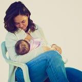 Breastfeeding. Vintage look Pretty young mum breastfeeding her baby Royalty Free Stock Image