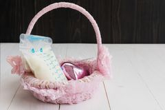 Breastmilk in storage bag on basket. Breastmilk in Breast milk storage bag and heart toy on pink weave rattan basket with wood background. Nutrition food for Royalty Free Stock Photos
