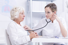 Breath in and breath out... Doctor checking senior patient's breath sound with a stethoscope royalty free stock photos