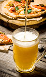 The breath of fresh beer being poured into glass. On the background of the pizza. Stock Photo