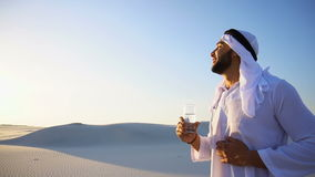 Breath of freshness of male Muslim in middle of dry climate of sandy desert. guy Arab drinks water from glass in open stock video