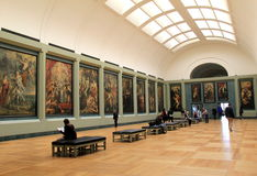 Breath-taking view of long room of masterpieces,The Louvre,2016. Amazing view of long,narrow room with benches for sightseers to take time to study the priceless Royalty Free Stock Photos