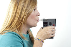 Breath test. A woman blowing into a police breath test machine Royalty Free Stock Photography